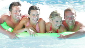 Group Of Friends On Holiday In Swimming Pool. Two couples paddle inflatable airbed across pool towards camera. Shot on Canon 5D Mk2 at at a frame rate of 25 fps stock video