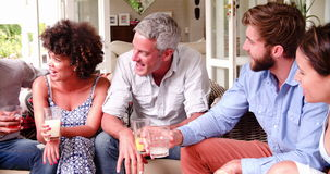 Group Of Friends At Home On Patio Talking Together. Group of friends at home sitting outdoors on patio with soft drinks talking - they make a toast together.Shot stock footage