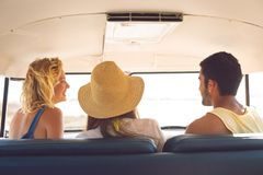 Group of friends interacting with each other in a camper van at beach. Rear view of group of diverse friends interacting with each other in a camper van at beach royalty free stock photos