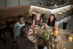 Group of friends interacting with each other while dining Stock Photos
