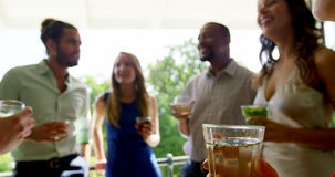 Group of friends interacting with each other while having drinks stock footage