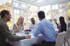 Group of friends interacting with each other while having lunch together Royalty Free Stock Photos