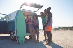 Group of friends interacting with each other near camper van at beach. Front view of young group of diverse friends interacting with each other near camper van royalty free stock photography