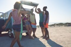 Group of friends interacting with each other near camper van at beach. Front view of young group of diverse friends interacting with each other near camper van royalty free stock images