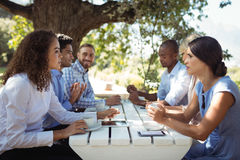 Group of friends interacting with each other. In outdoors restaurant Stock Image