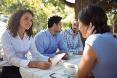 Group of friends interacting with each other. In outdoors restaurant Royalty Free Stock Image