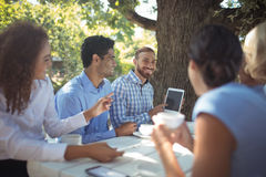 Group of friends interacting with each other. In outdoors restaurant Royalty Free Stock Photography