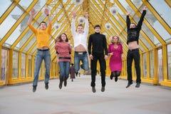 Group of friends jump on footbridge Royalty Free Stock Photo