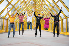 Group of friends jump on footbridge Royalty Free Stock Photo