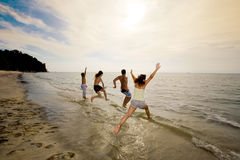 Group of friends jumping into the sea. Group of friends having fun jumping into the sea on sunset Stock Images