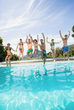 Group of friends jumping in swimming pool Royalty Free Stock Photo