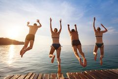 Happy beach holidays, group of friends jumping to water. Group of friends jumping to the sea from the pier, happy beach holidays Royalty Free Stock Images