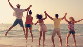 Group of friends jumping together on the beach stock video footage