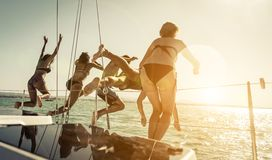 Group of friends jumping in the water from the boat Stock Image