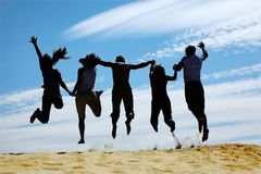 Group of friends jumps on sand, rear view Royalty Free Stock Image