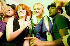 Group of friends at karaoke party. Group of friends (male and female, diversity) at a party in a club doing karaoke Stock Photo