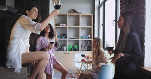 Group of friends ladies very attractive enjoy their bachelorette party at home in a modern studio design they drinking. Some wine glasses and feeling happy. 4k stock video