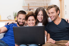 Group of friends laughing at a laptop. Group of friends sitting together on a sofa laughing at information on a laptop computer Stock Image