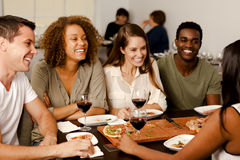 Group of friends laughing in a restaurant. Mixed-race group of friends laughing together in a pizza restaurant Royalty Free Stock Image