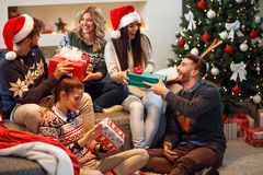 Friends laughing and sharing Christmas gifts. Group of friends laughing and sharing Christmas gifts Royalty Free Stock Image