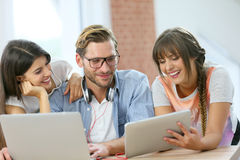 Group of friends laughing using tablet and laptop Stock Photo