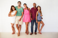 Group Of Friends Leaning Against White Wall Stock Photography
