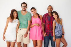 Group Of Friends Leaning Against White Wall Stock Photo