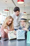 Friends look curiously into their shopping bags royalty free stock photos