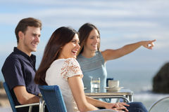 Group of friends looking at horizon in a restaurant. Group of friends laughing and looking at horizon in a restaurant on the beach with the ocean in the Royalty Free Stock Photo