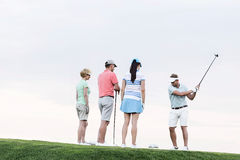 Group of friends looking at man playing golf against clear sky Stock Photos