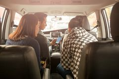 Group of friends looking a map on cell phone in car road trip concept. stock image