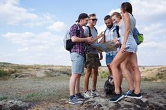 Group of friends looking at map and discussing outdoors. Friends go at hiking, forest, recreation, love active lifestyle Stock Image