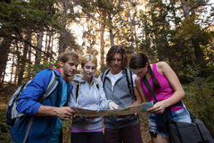 Group of friends looking at the map while hiking Royalty Free Stock Photos