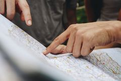 Group of friends looking at a map together travel and teamwork concept. Group of friends looking at a map together Group of friends looking at a map together Stock Image