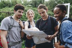 Group of friends looking at a map together travel and teamwork concept Royalty Free Stock Photo