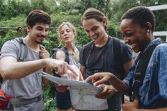 Group of friends looking at a map together travel and teamwork concept Stock Images