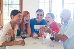 Group of friends looking at the mobile phone royalty free stock photography