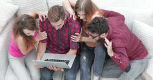 Group of friends looking at the photo on the laptop. Royalty Free Stock Photo
