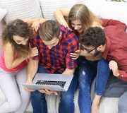 Group of friends looking at the photo on the laptop. View from the top. a group of friends looking at the photo on the laptop Royalty Free Stock Image