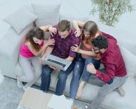 Group of friends looking at the photo on the laptop. View from the top. a group of friends looking at the photo on the laptop Stock Photography