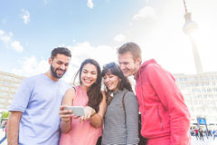 Group of friends looking at smart phone in Berlin Stock Photos