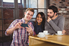 Group of friends looking at a smartphone Royalty Free Stock Photo