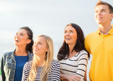 Group of friends looking up on the beach. Summer, holidays, vacation, happy people concept - group of friends looking up on the beach Royalty Free Stock Photography