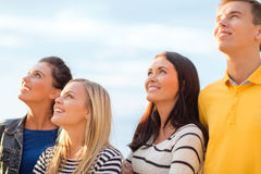 Group of friends looking up on the beach. Summer, holidays, vacation, happy people concept - group of friends looking up on the beach Royalty Free Stock Photos
