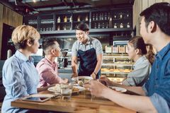 Group of friends looking at waiter serving food royalty free stock photo