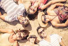 Group of friends lying on the beach. In a sunny day. concept about mixed race friends and vacations Royalty Free Stock Image