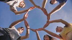 A group of friends makes a circle from the palms of their hands.