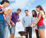 Group of friends making barbecue on the beach. Summer holidays, food and drink, happy people concept - group of friends making barbecue on the beach royalty free stock photo