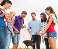 Group of friends making barbecue on the beach. Summer, holidays, vacation, happy people concept - group of friends having picnic and making barbecue on the beach royalty free stock photography