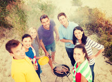 Group of friends making barbecue on the beach. Summer, holidays, vacation, happy people concept - group of friends having picnic and making barbecue on the beach stock images